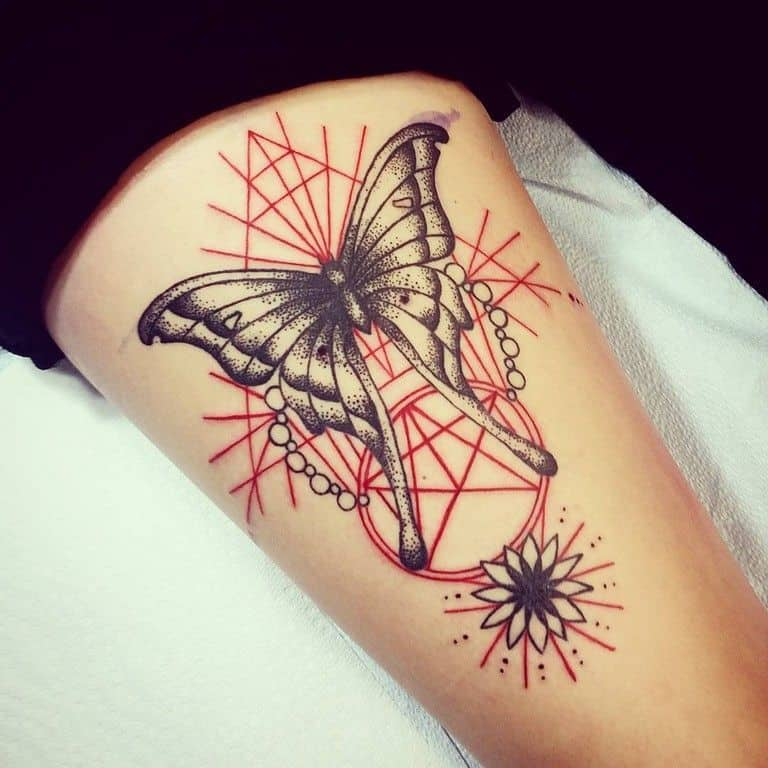 large black and color tattoo on thigh of a butterfly with red geometric lines and shapes behind it