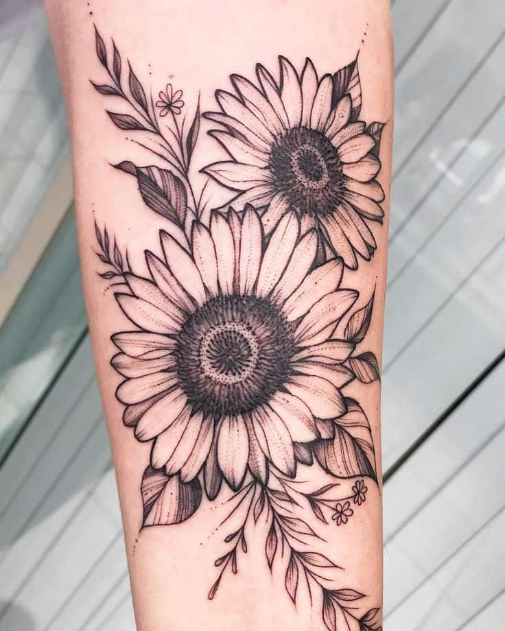 large black and grey line tattoo on forearm of two realistic sunflowers with leaves and vines around them