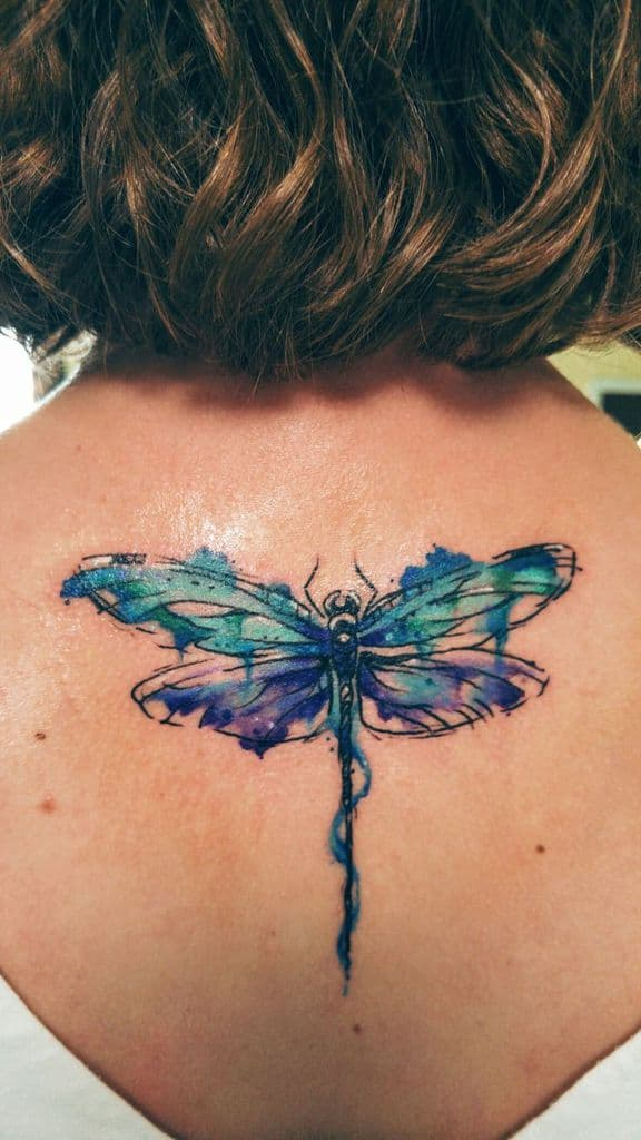 The dreamy dragonfly with all its lively colors on the woman's back
