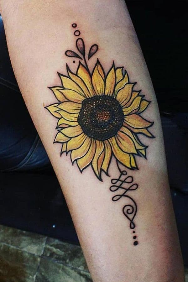 medium-sized traditional color tattoo on woman's arm of a sunflower with filigree