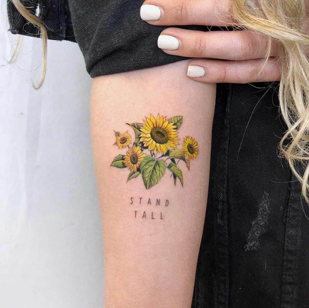 medium-sized color tattoo on woman's forearm of realistic bouquet of sunflowers with leaves and stand tall quote