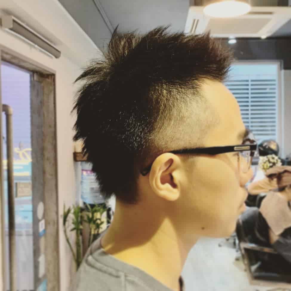 A Mohawk Haircut For Men With A Balding Head. It Features Short Hair On Top And Bald Faded Sides With Lines On Either Side