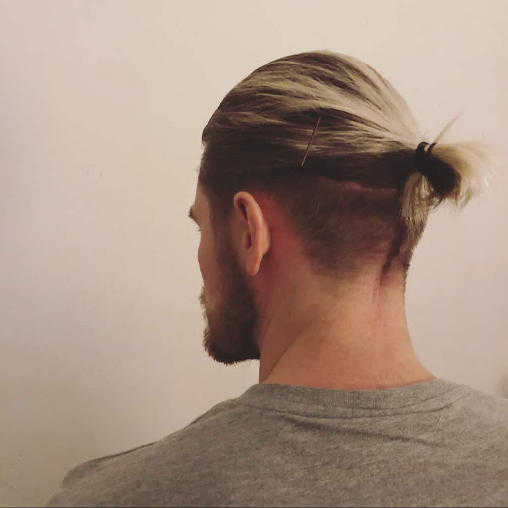 A Man Bun Hairdo With Undercut And Spikes Sticking Out From The Knot