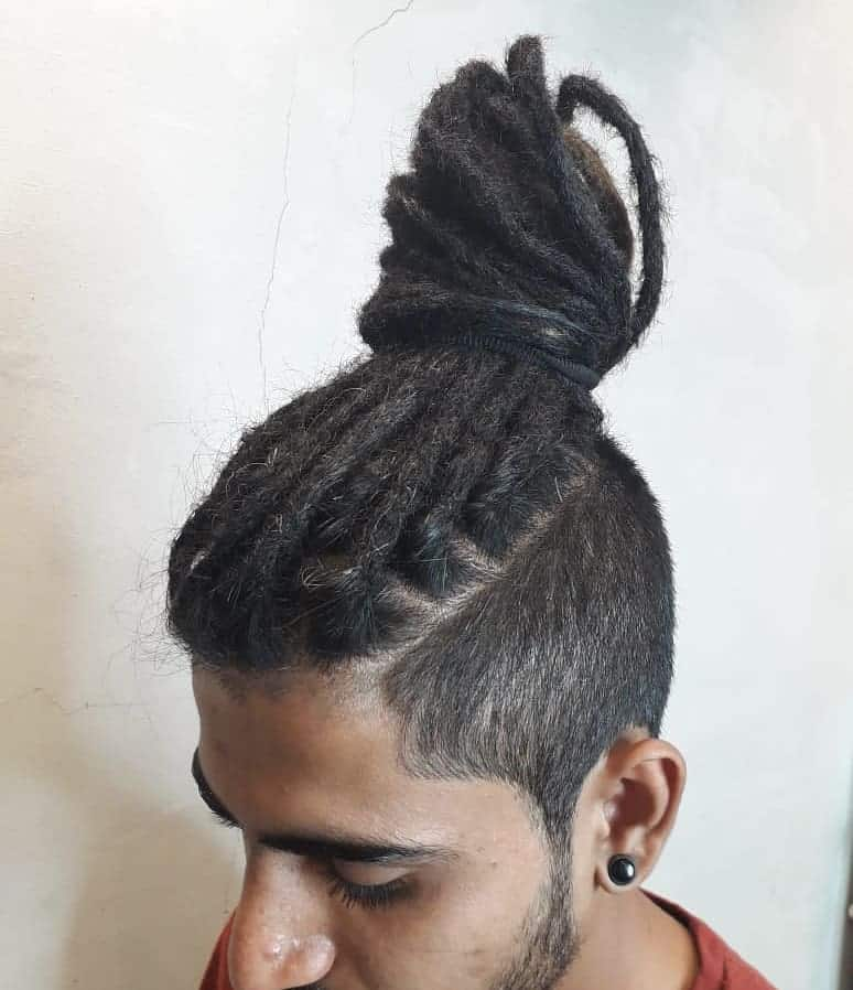 A Man Bun Hairstyle Paired With Undercut And Dreads