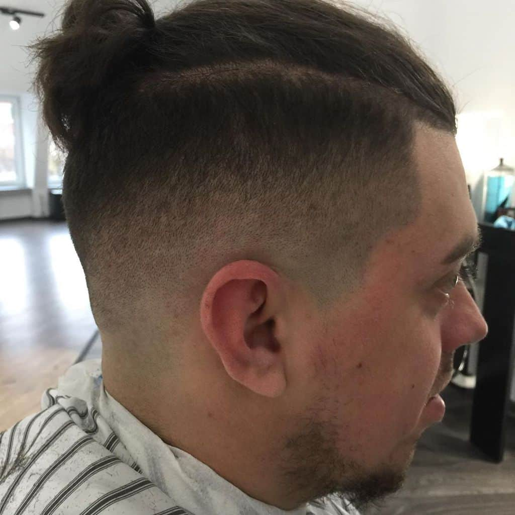 A Man Bun Hairstyle Paired With Undercut And Taper Fade. A Standout Look For Stylish Men