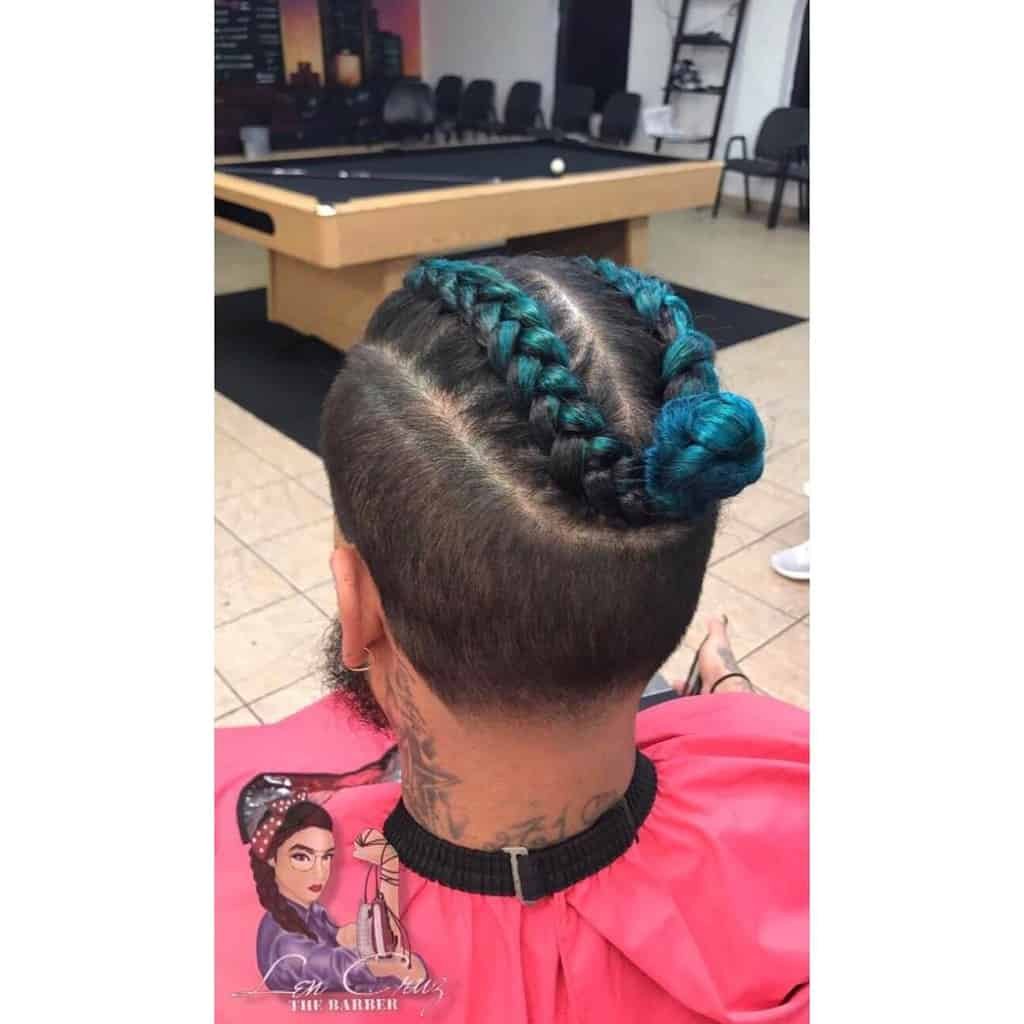 A Man Bun Undercut Style Featuring Long Dyed Hair On Top And Undercut With Natural Shade
