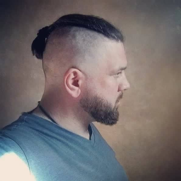 A Man Bun Undercut Style Paired With Clean Shaved Part