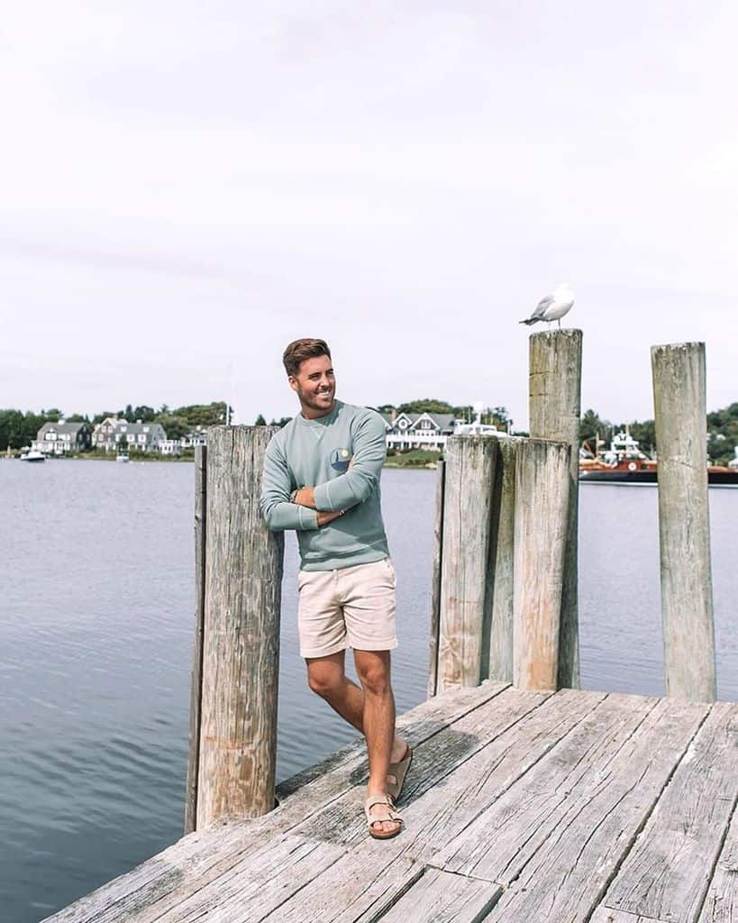 A Man Wearing A Bluish Green Crewneck Sweater While Standing On A Pier With His Arms Crossed