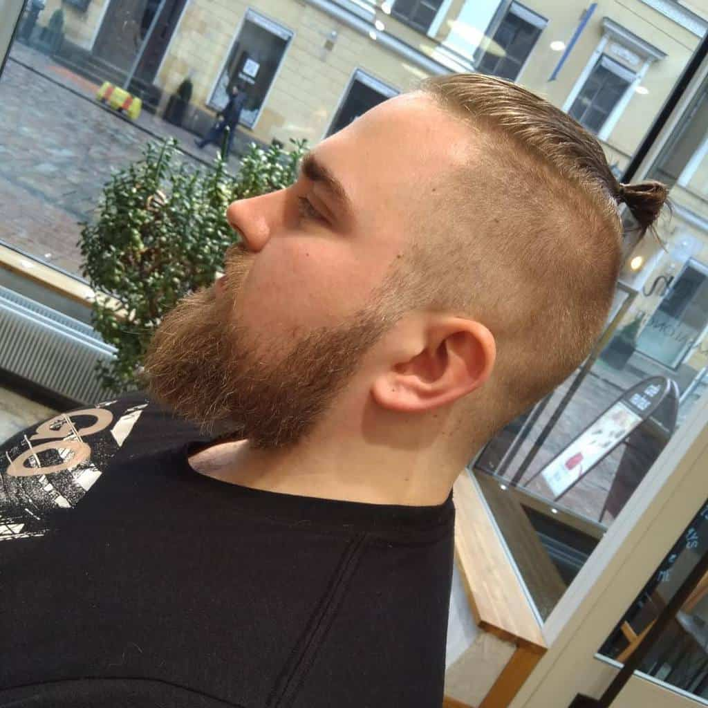 A Man Wearing A Man Bun Style With Undercut With Some Stray Locks In The Front
