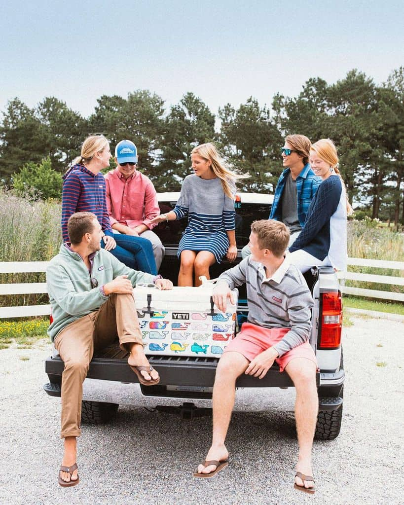 A Man Wearing Cuffed Chinos With A Large Group Of Friends In The Bed Of A Pickup Truck