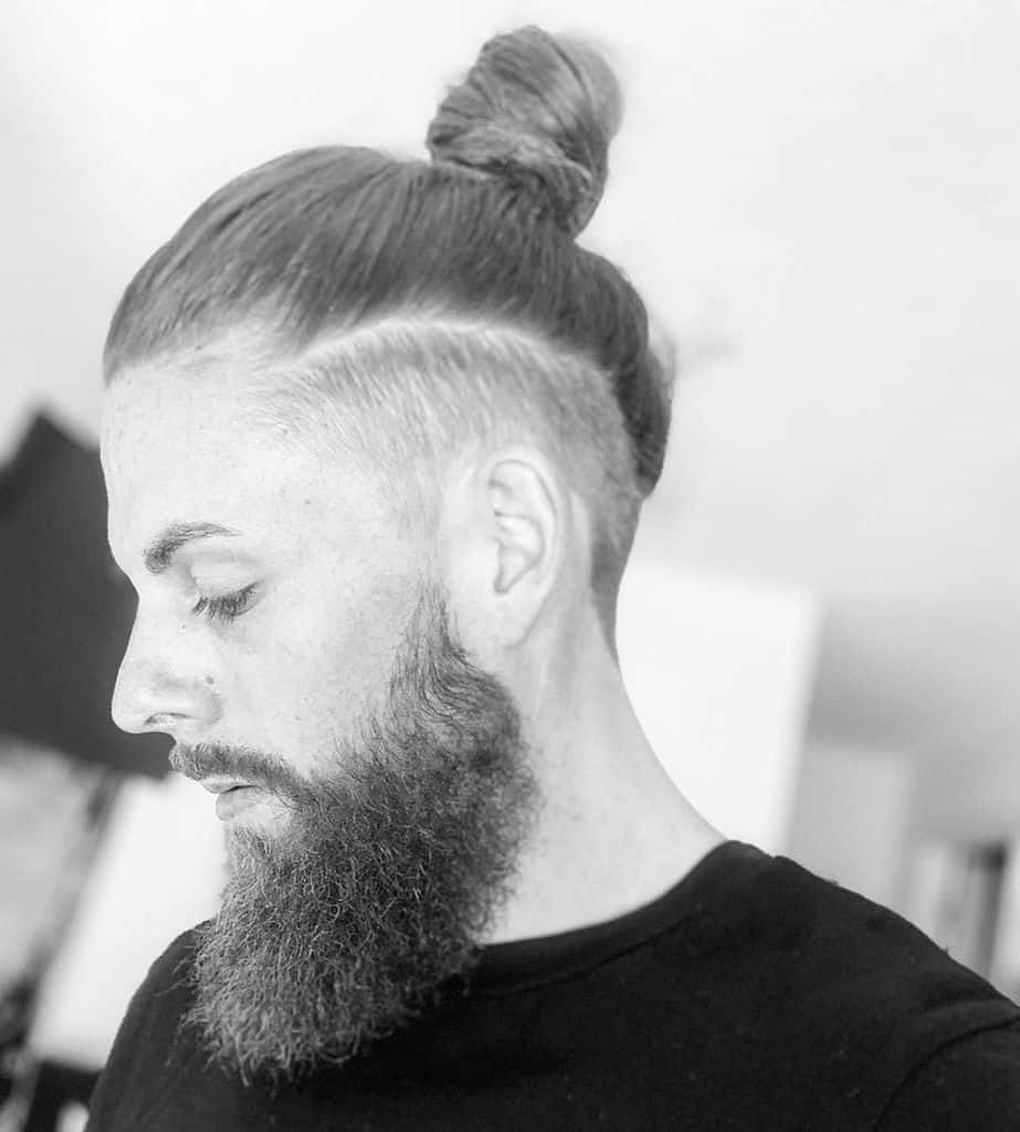 A Man With A Thick Beard Wearing A Man Bun Undercut. The Two Matches Each Other Seamlessly