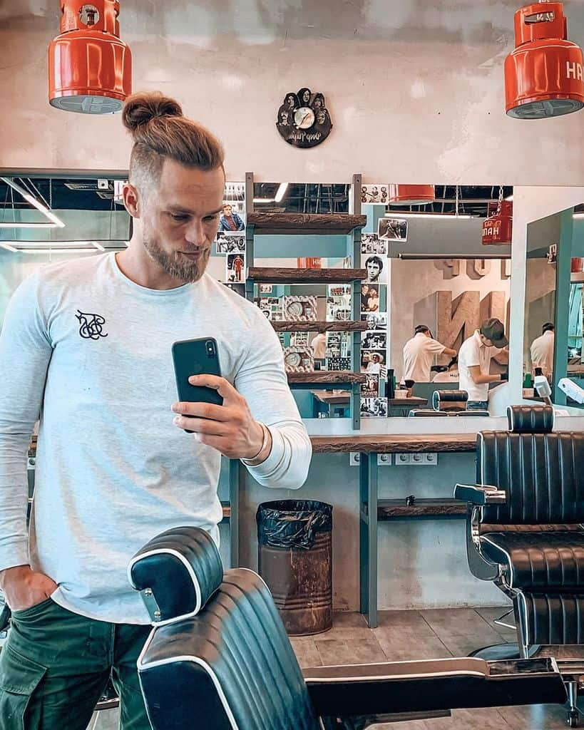 A Modern Man Bun With Long Hair Styled Backward Into A Bun. The Hair On The Sides Is Shaved Into A Short Crop