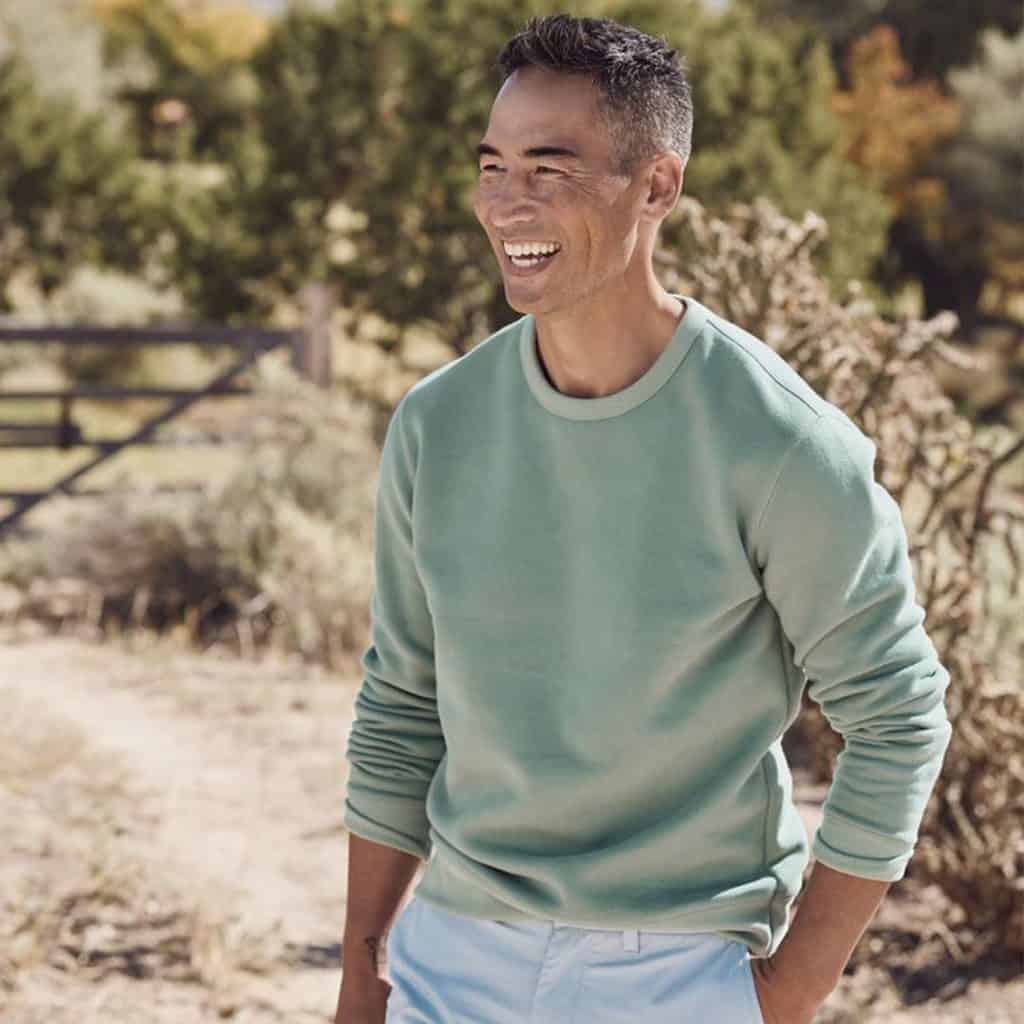 A Smiling Man Wearing A Classic Light Colored Crew Neck Sweater And Chinos
