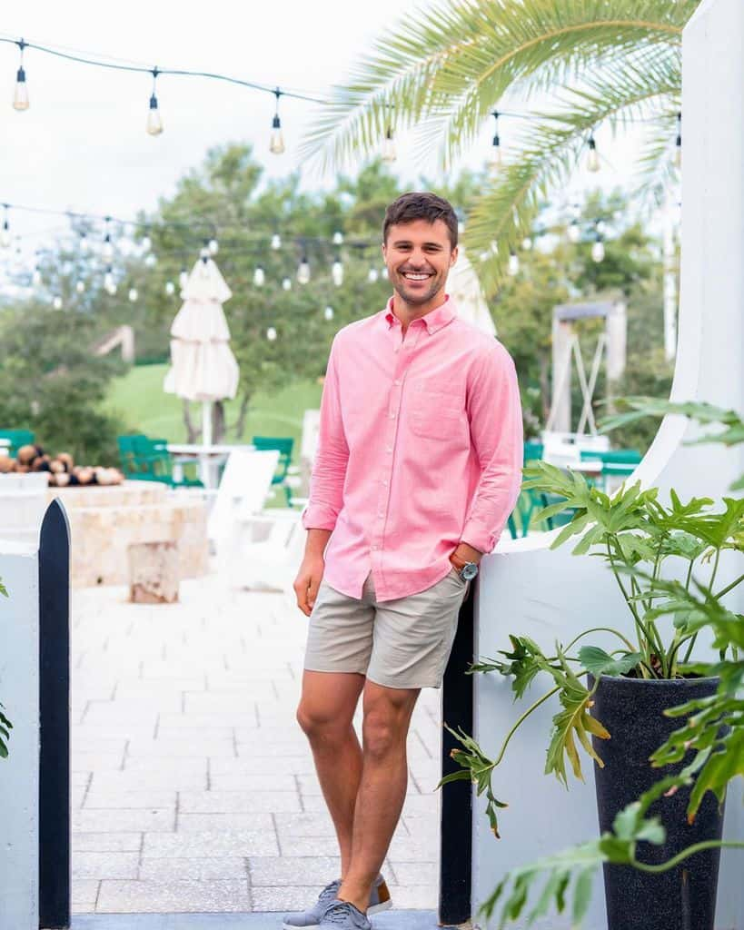 A Smiling Man Wearing A Solid Pink Button Down Shirt And Chino Shorts