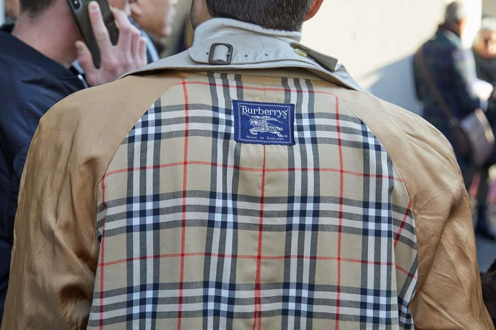 A man wears a Burberry trench coat at a fashion show in Milan, Italy.