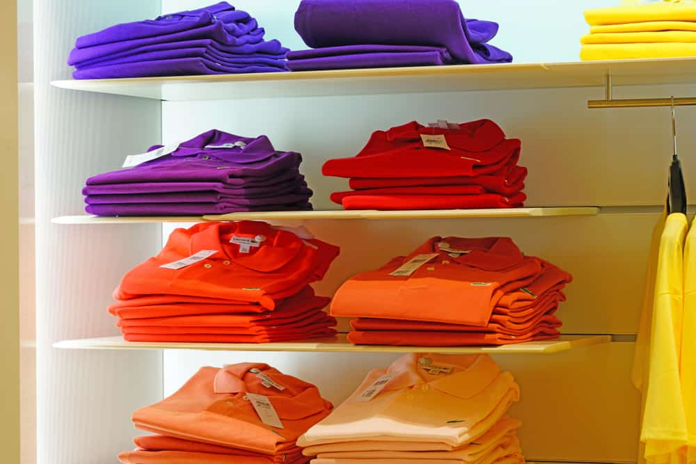 Colorful polo shirts stacked on a shelf in a Lacoste store