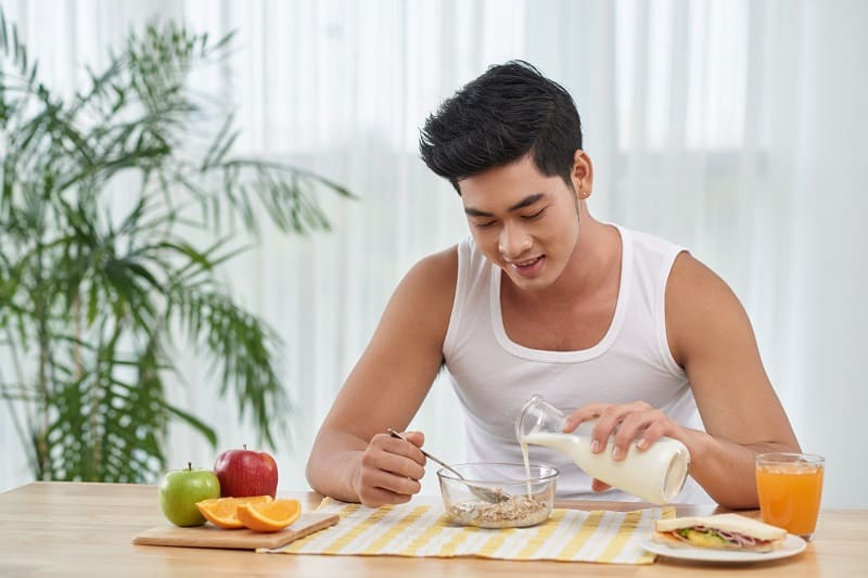 Smiling,Young,Man,Adding,Milk,In,His,Granola