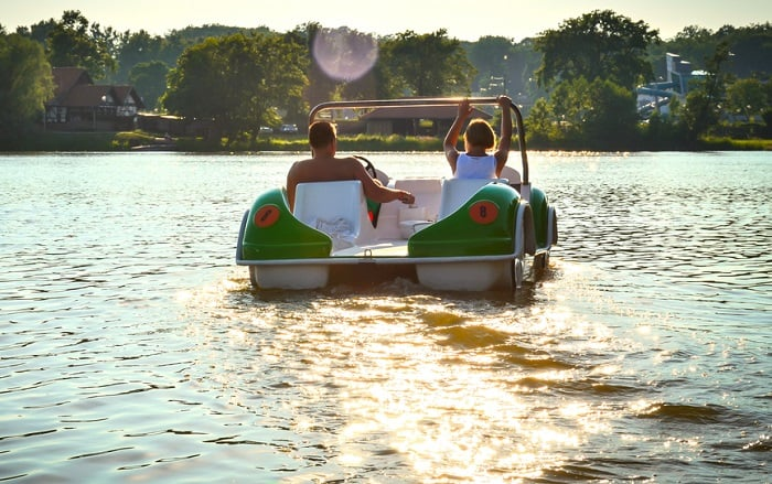 Couple In Pedal Boat On Lake