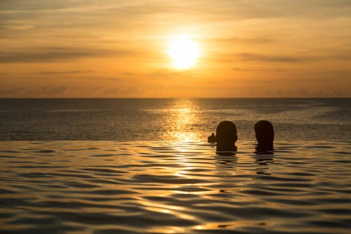 Couple Swimming At Sunset