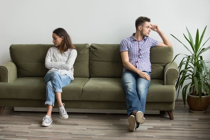 Couple sitting on opposite ends of sofa looking in different directions