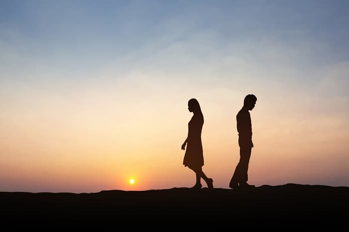 Silhouettes of man and woman walking apart in front of sunset