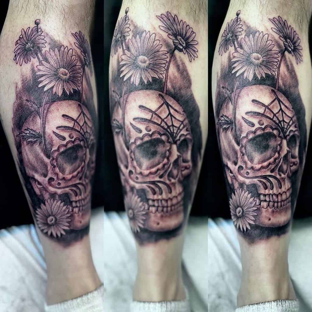 Calf tattoo realistic black and grey skull with Day of the Dead markings surrounded by daisies