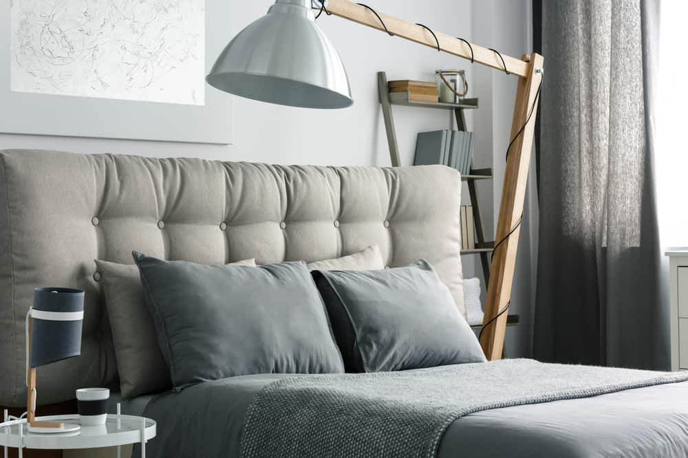 Grey,Bed,With,Quilted,Headboard,And,Big,Wooden,Lamp