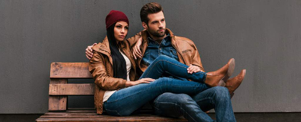 Fashionable couple sitting on bench in autumn