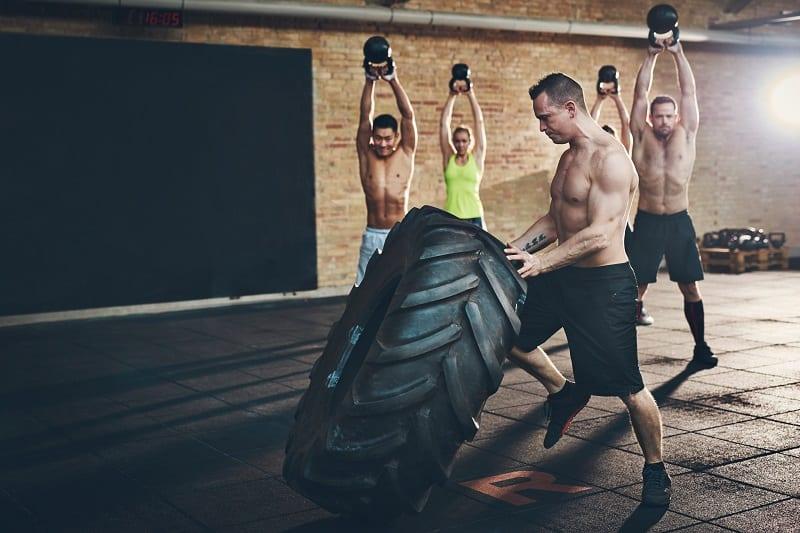 Muskulös, mit nacktem Oberkörper, Mann, in Bewegung, groß, Reifen, während, vier, andere, sportlich