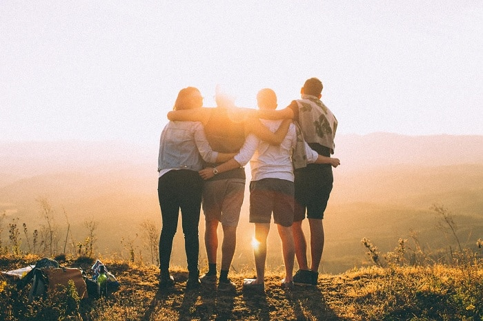 Friends Standing On Hill At Sunset