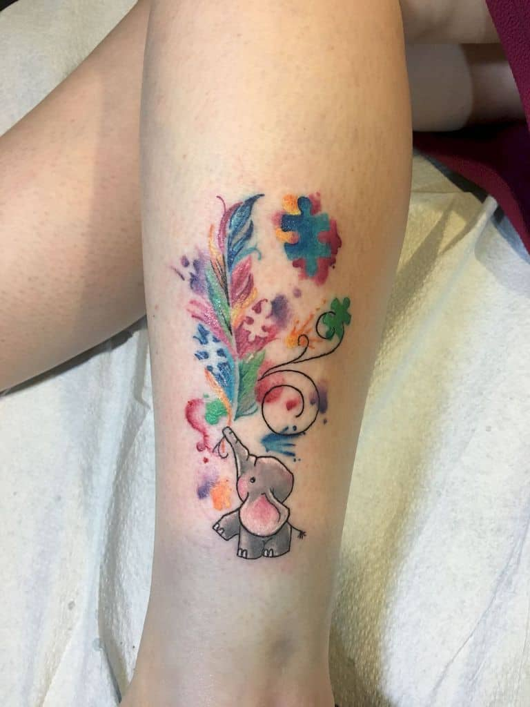 : Full color calf tattoo with baby elephant holding watercolor feather with puzzle pieces and line work flourishes.