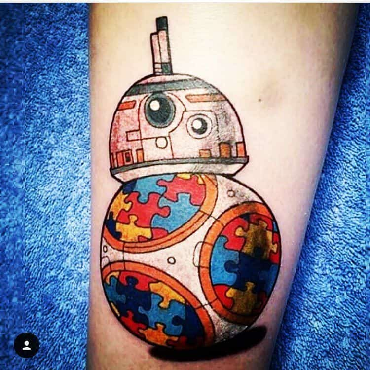 Full color forearm tattoo of Star Wars droid with Autism Awareness Puzzle designs.