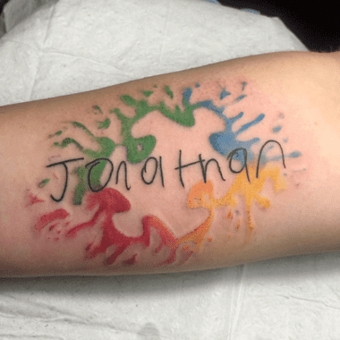"""Full color forearm tattoo of watercolor splashes a negative space puzzle piece and child-like script: """"Jonathan""""."""