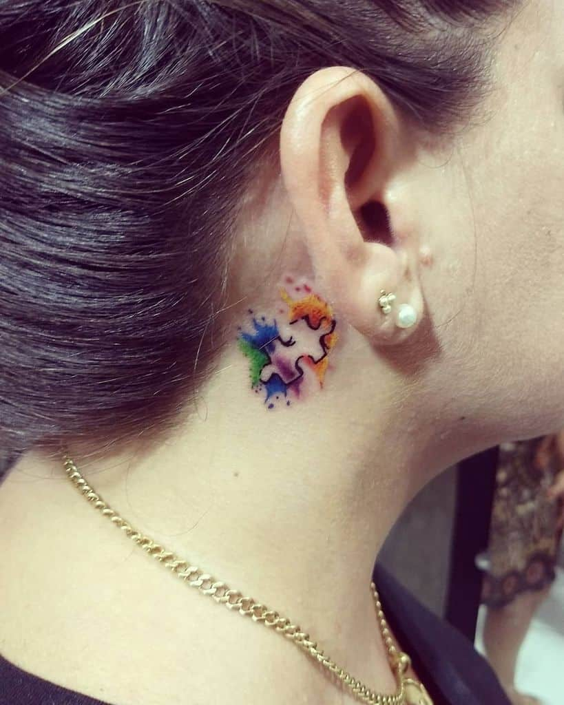 Full color puzzle piece tattoo behind the ear with watercolor splashes.