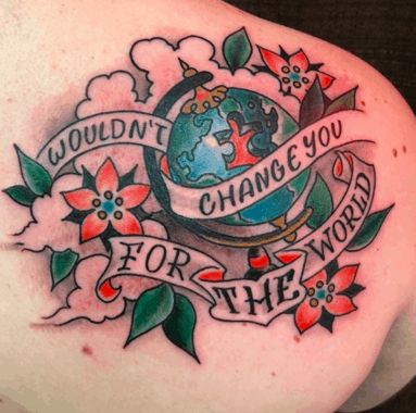 Full color shoulder blade tattoo with American traditional flowers and inspirational quote with globe missing a puzzle piece.