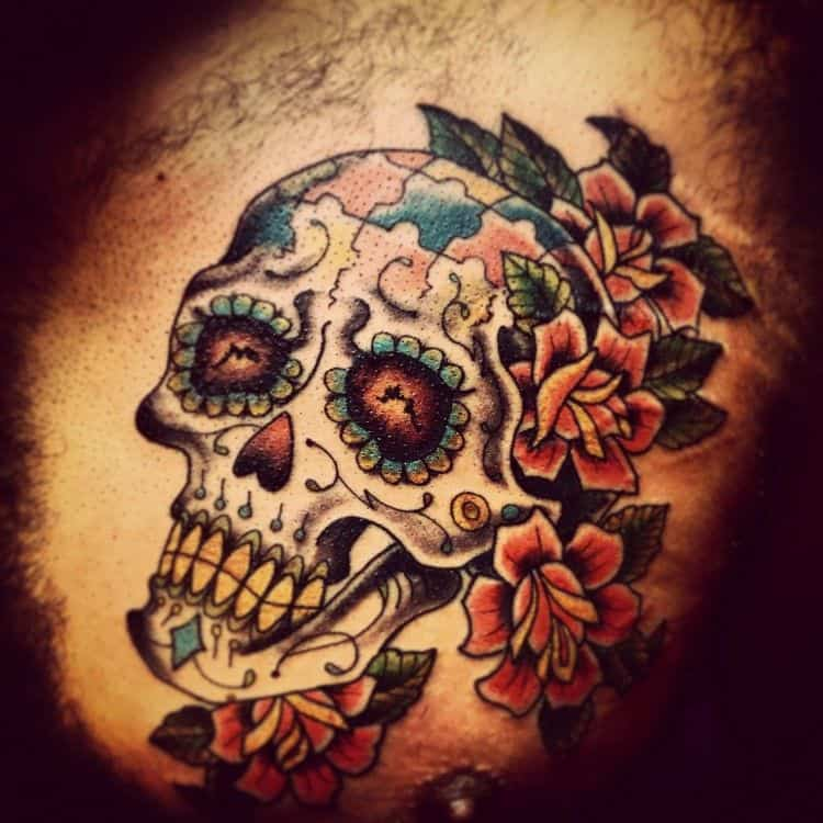 Full color tattoo of Day of Dead skull with multi-colored puzzle pieces and roses.