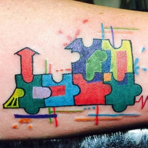 Full color tattoo of locomotive with puzzle designs watercolor splashes and an EKG reading.