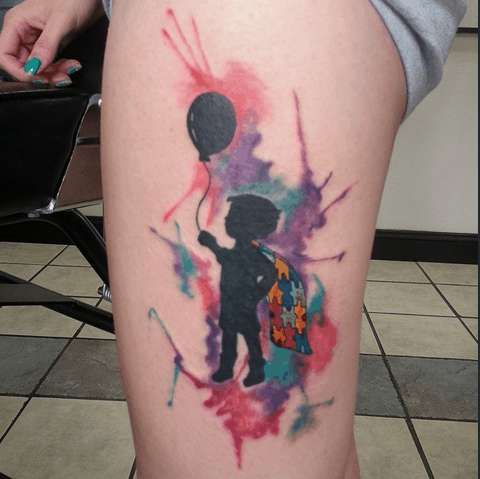 Full color thigh tattoo of child's silhouette with balloon and puzzle piece cape with watercolor splashes.