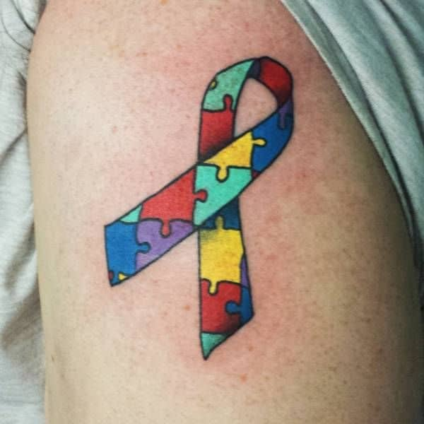 Full color upper-arm tattoo of Autism Awareness Puzzle ribbon.