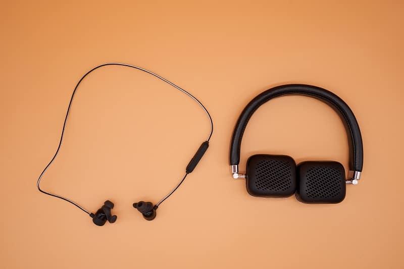 Different,Type,Of,Headphones,On,Orange,Paper,Background