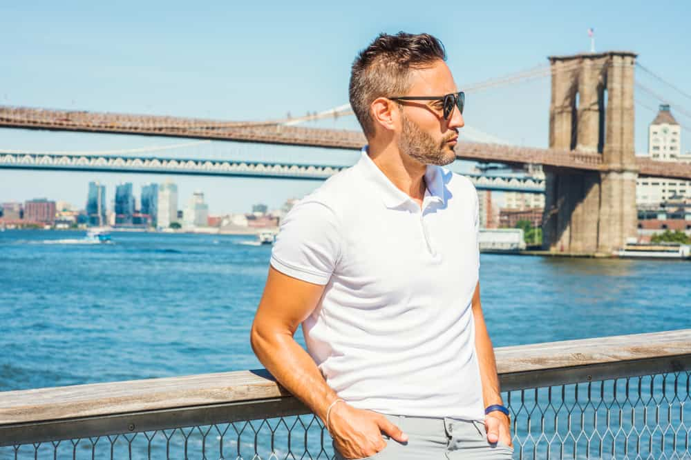 A man wearing a smooth-knit white polo shirt with the Brooklyn Bridge in the background