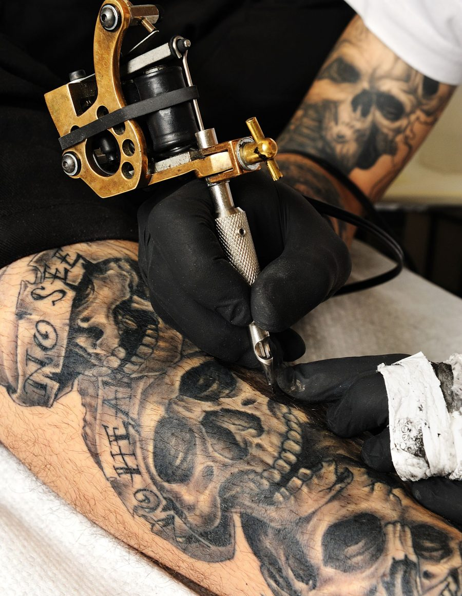 Man Being Tattooed with Skulls