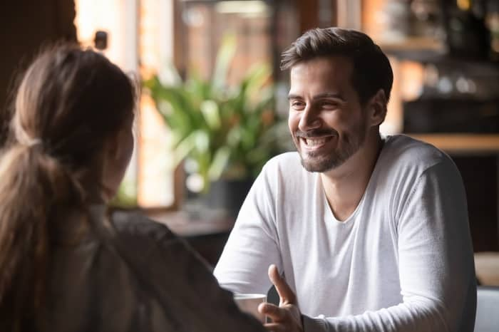 Man smiling while talking with a woman