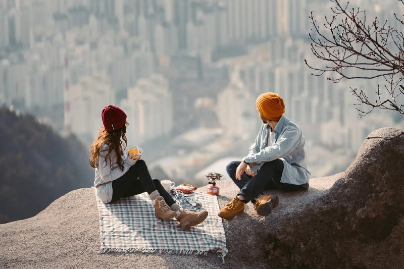 Couple Having Picnic Date With View of City
