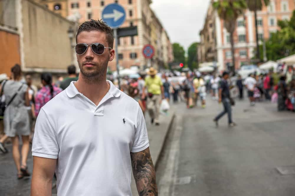 Man in a white Ralph Lauren polo and sunglasses on a street in Italy