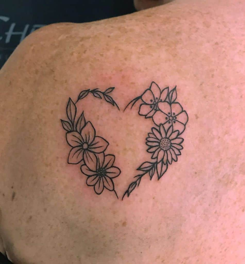 Shoulder tattoo black and grey fine line traditional daisies and other flowers forming heart-shaped wreath