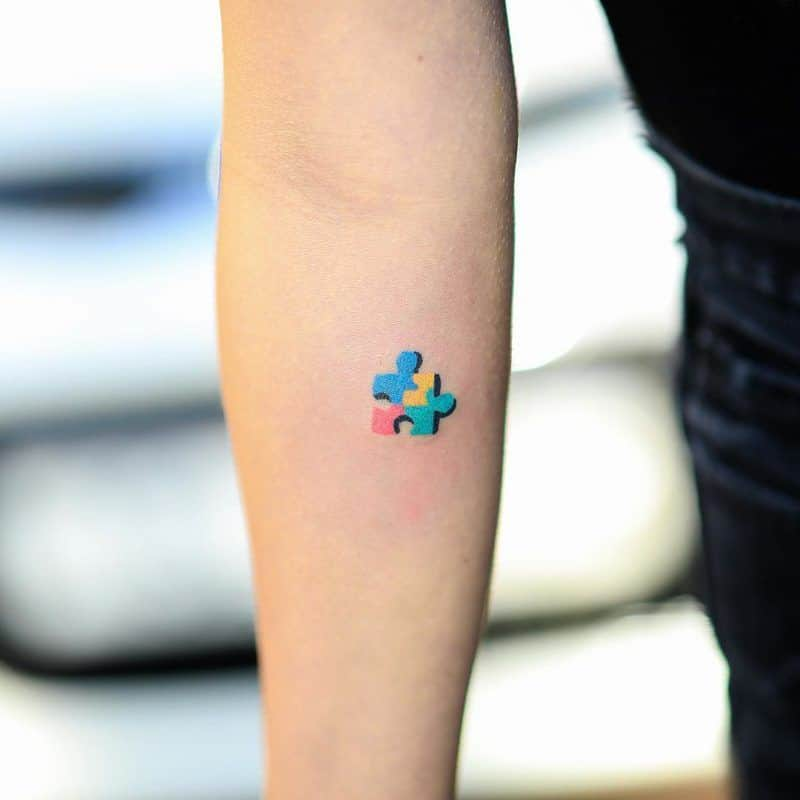 Small full color forearm tattoo of multi-colored puzzle piece with black drop shadow.