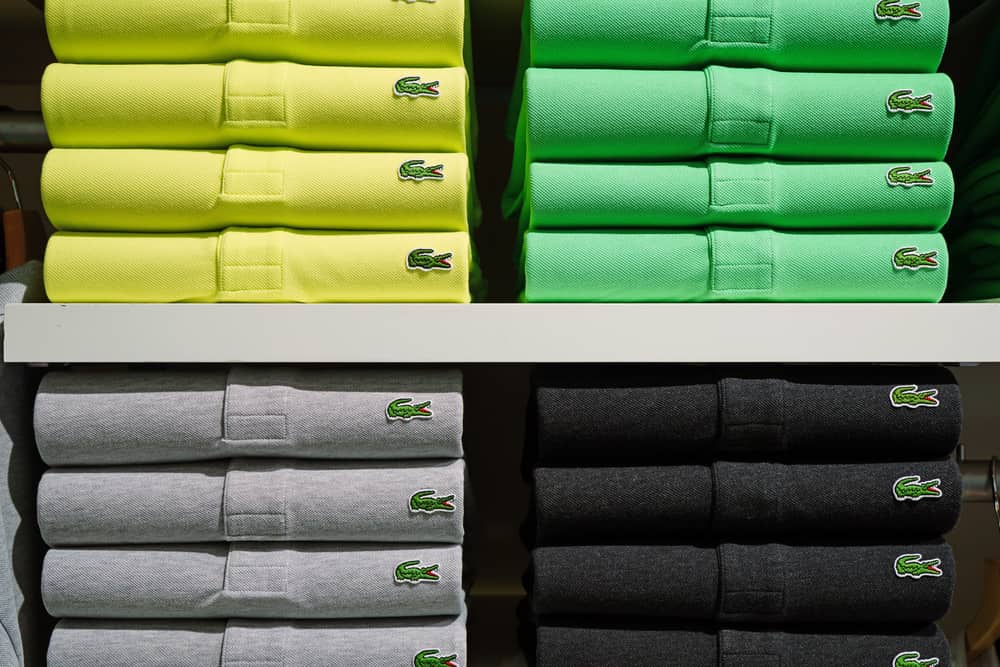 Stacks of Lacoste polos in various colors lined up on a shelf