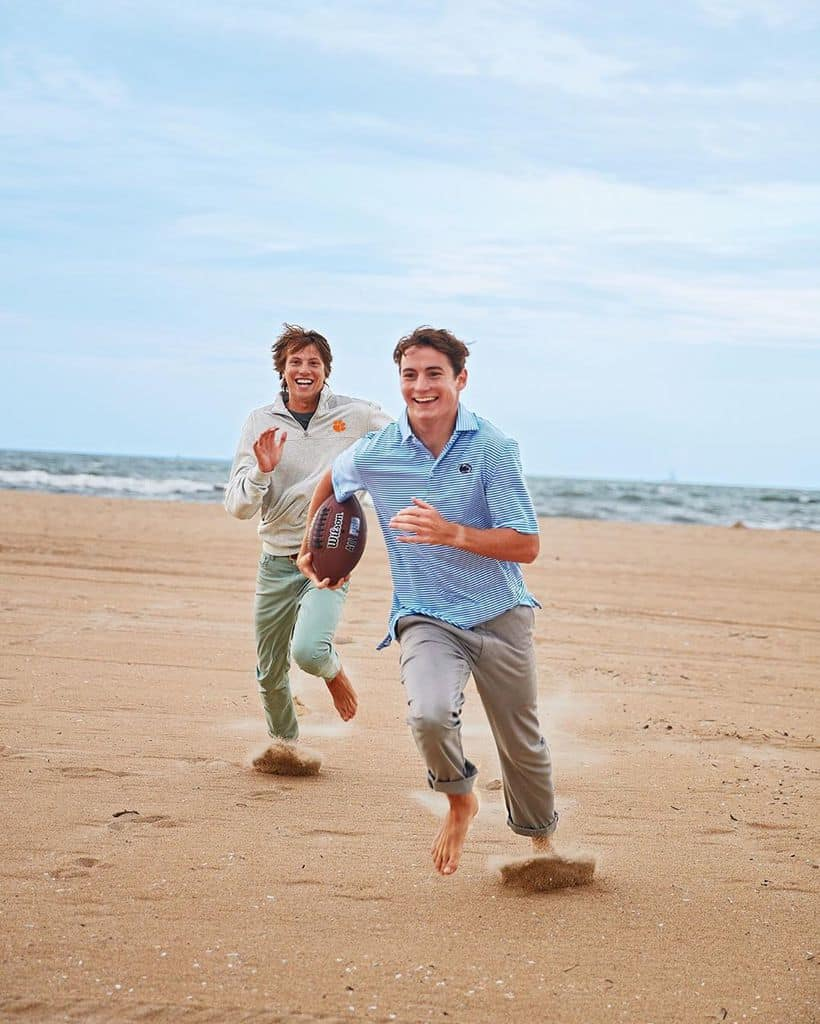 Two Men Playing Football On The Beach And Both Wearing Cuffed Chinos