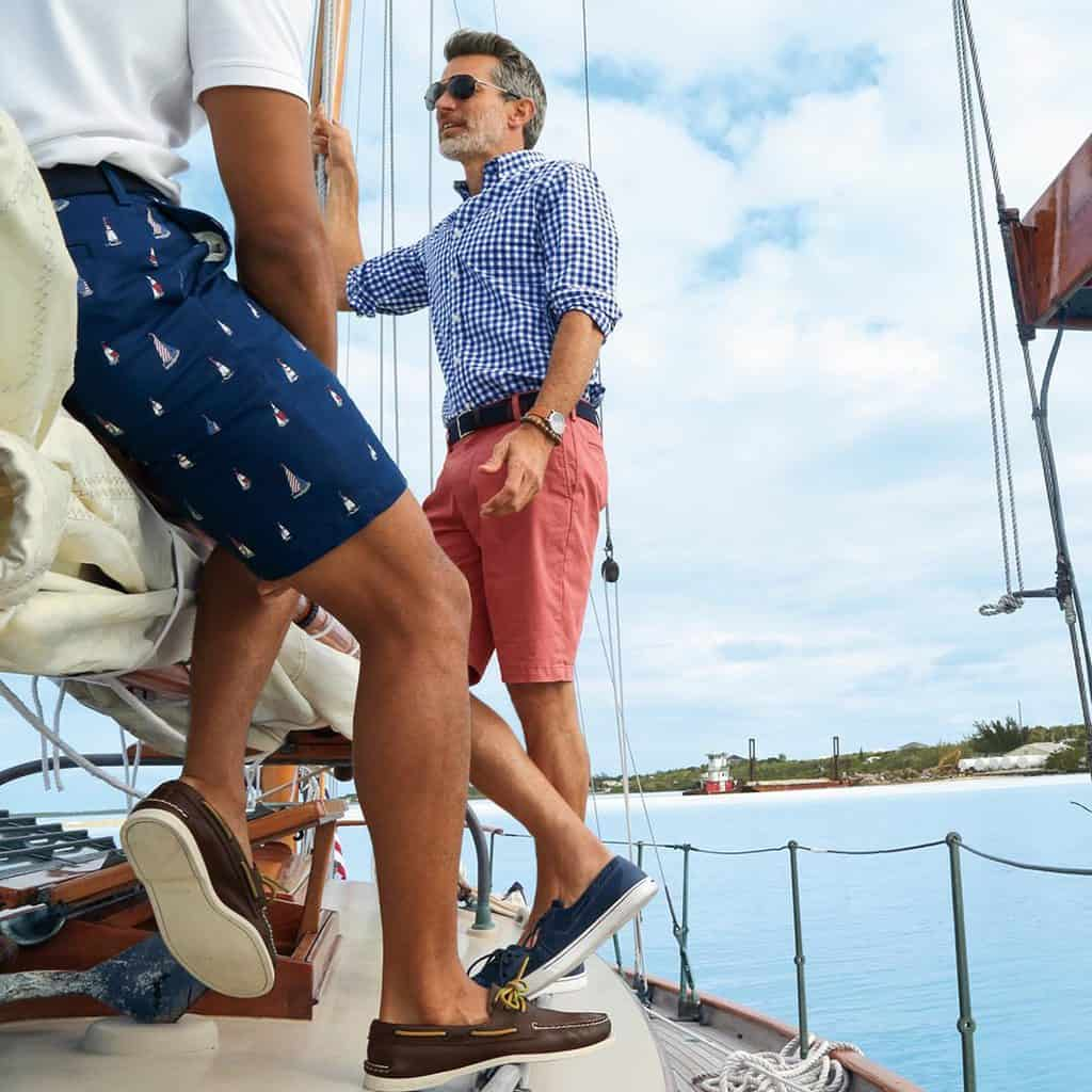 Two Men Wearing Loafers With No Socks And Having A Conversation On A Boat